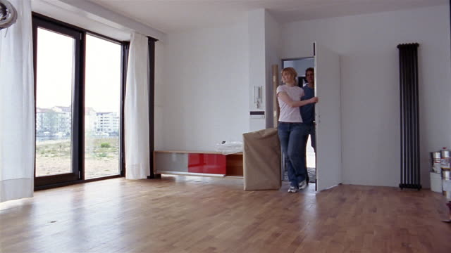 vídeos de stock e filmes b-roll de medium shot dolly shot couple entering unfurnished apartment and hugging - amador