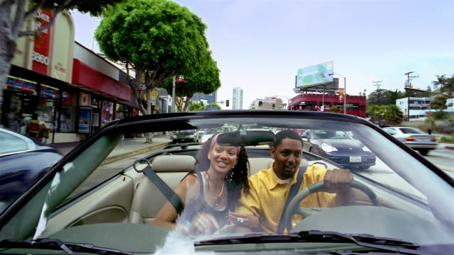 Medium shot dolly shot couple in convertible driving along Sunset Boulevard and sightseeing / Hollywood, California