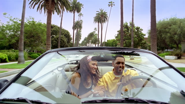 medium shot dolly shot couple in convertible driving down palm tree-lined street / beverly hills, california - ford motor company stock videos and b-roll footage