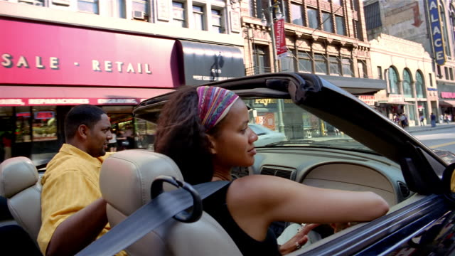 Medium shot dolly shot couple in convertible driving downtown / dancing to music / Los Angeles, California
