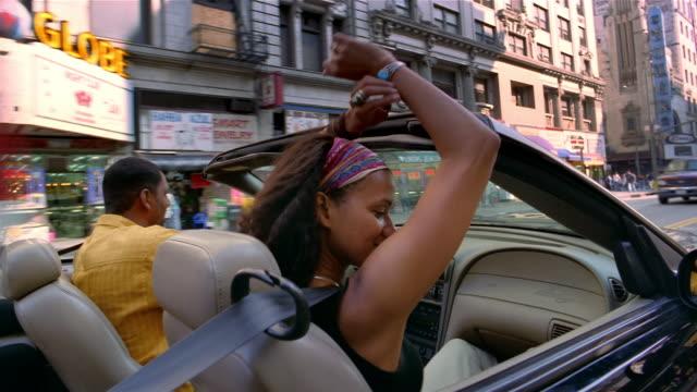 medium shot dolly shot couple in convertible driving downtown / dancing to music / los angeles, california - シートベルト点の映像素材/bロール