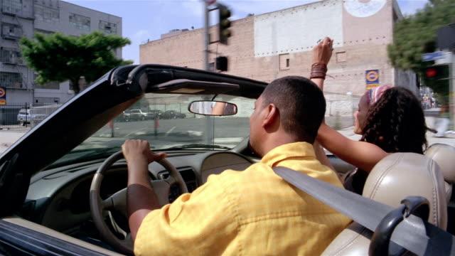 medium shot dolly shot couple in convertible driving downtown / singing and bopping to music / los angeles, california - シートベルト点の映像素材/bロール