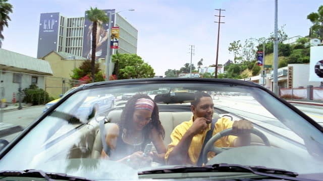 vídeos de stock, filmes e b-roll de medium shot dolly shot couple in convertible driving on sunset boulevard / talking on phone / hollywood, california - 2005