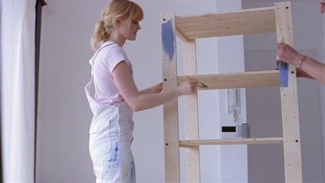 stockvideo's en b-roll-footage met medium shot dolly shot couple painting shelf unit - doe het zelven