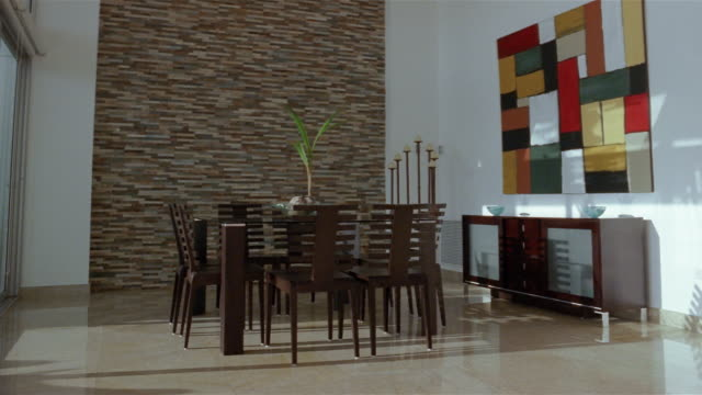 medium shot dolly shot dining room table and chairs / abstract painting on the wall - 花瓶点の映像素材/bロール