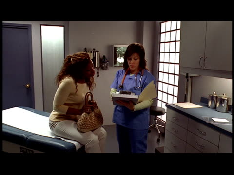 medium shot dolly shot doctor talking to patient in examination room / looking at chart - letterbox format stock videos & royalty-free footage