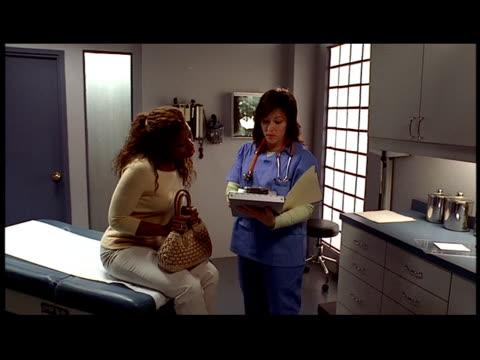 vídeos y material grabado en eventos de stock de medium shot dolly shot doctor talking to patient in examination room / looking at chart - formato buzón