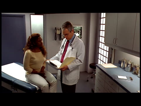 vídeos de stock, filmes e b-roll de medium shot dolly shot doctor talking  to patient sitting on exam table in doctor's office / holding her arm - braço humano
