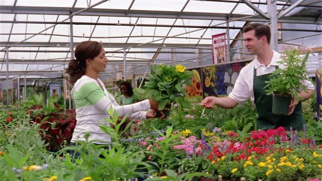Medium shot dolly shot employee helping woman shopping for plants in garden center
