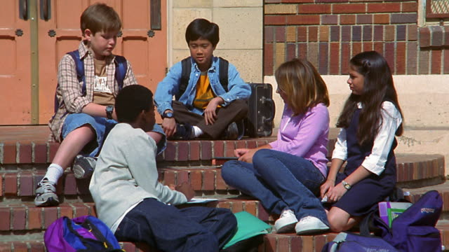 medium shot dolly shot ethnically diverse children sit, talk and read book on stairs in front of school - in front of stock videos and b-roll footage