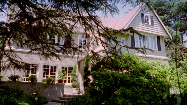 Medium shot dolly shot exterior of large house partially obscured by plants and trees