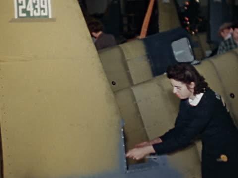 1943 medium shot dolly shot factory floor with men and women working on airplanes - gesellschaftliche mobilisierung stock-videos und b-roll-filmmaterial