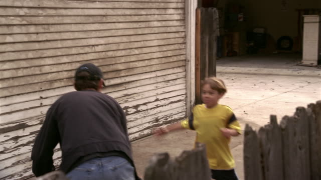 medium shot dolly shot father and son playing one-on-one basketball in driveway - driveway stock videos & royalty-free footage