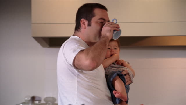 medium shot dolly shot father carrying baby / picking up coffee cup and drinking / sitting baby at breakfast table - genderblend stock videos & royalty-free footage