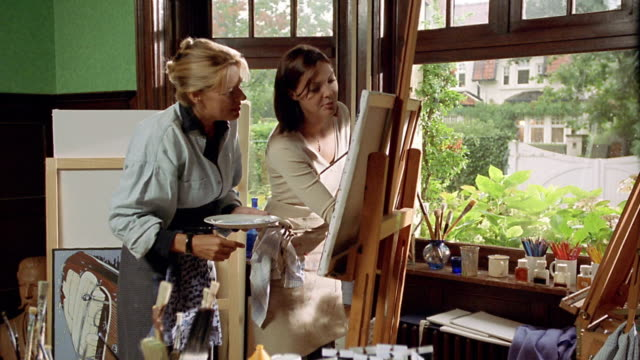 medium shot dolly shot female artist instructing young woman while painting on easel inside studio - teaching stock videos & royalty-free footage