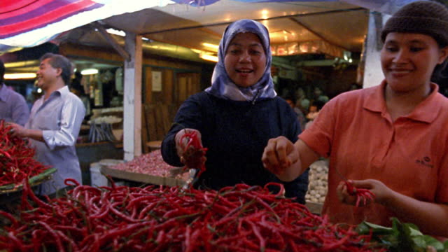 medium shot dolly shot female vendors selling peppers and spices in market / bukittinggi, west sumatra - malaysian ethnicity stock videos & royalty-free footage