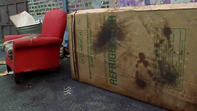 Medium shot dolly shot from alleyway to person sleeping in cardboard box
