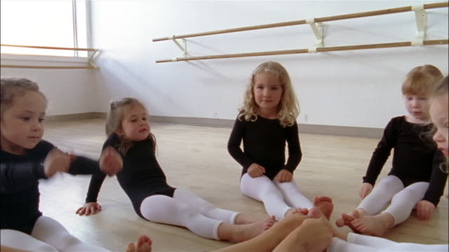 medium shot dolly shot girls wearing leotards sitting in a circle and pointing their toes / drawing their knees to their chests in ballet class - little girls bare feet stock videos and b-roll footage