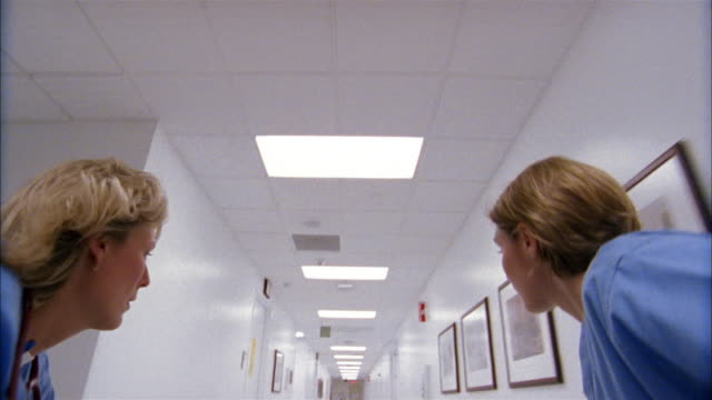 Medium shot dolly shot gurney point of view of patient wheeling down hospital hallway by two women wearing scrubs