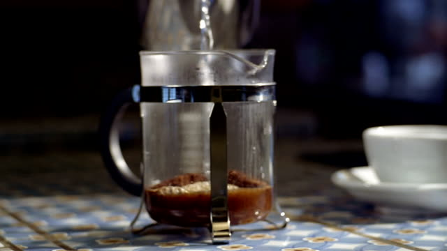 medium shot dolly shot hot water being poured over coffee in french press - やかん点の映像素材/bロール