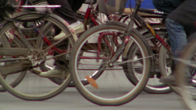 vidéos et rushes de medium shot dolly shot large group of bicycles on street with traffic passing in foreground / chengdu, china - chine