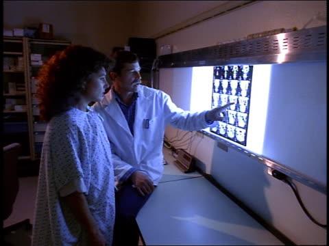 medium shot dolly shot male doctor explaining x rays to female patient in hospital - untersuchungskittel stock-videos und b-roll-filmmaterial