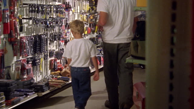 vídeos y material grabado en eventos de stock de medium shot dolly shot man and two boys picking up tools at hardware store - ferreteria