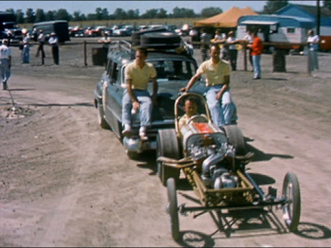 vídeos de stock, filmes e b-roll de 1959 medium shot dolly shot man driving buggy and pulling another car / two men sitting on hood of race car - hot rod