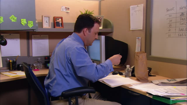 Medium shot dolly shot man working and eating brown bag lunch at desk in cubicle