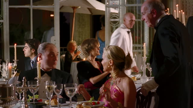 stockvideo's en b-roll-footage met medium shot dolly shot mature wealthy couple in evening wear having dinner in fancy restaurant - elegantie