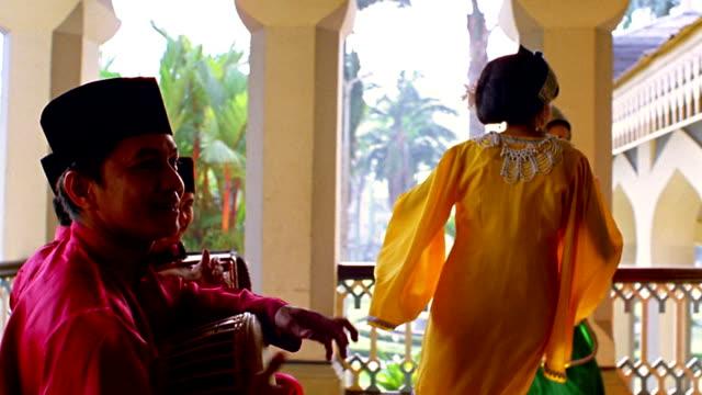 Medium shot dolly shot men play instruments and women perform traditional dance / Maimoon Palace, Medan, North Sumatra