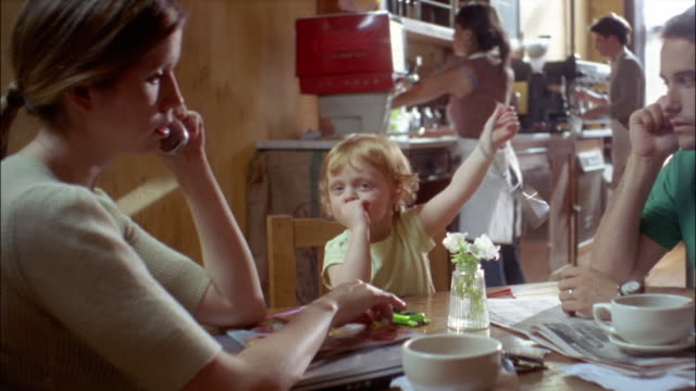 medium shot dolly shot mother and father talking on cell phones as little girl swings camera back and forth in cafe - showing off stock videos & royalty-free footage