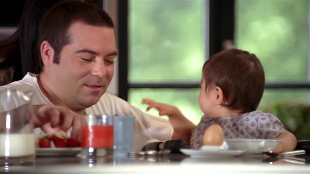 Medium shot dolly shot mother kissing father (eating strawberry) on cheek at breakfast table / smiling at baby