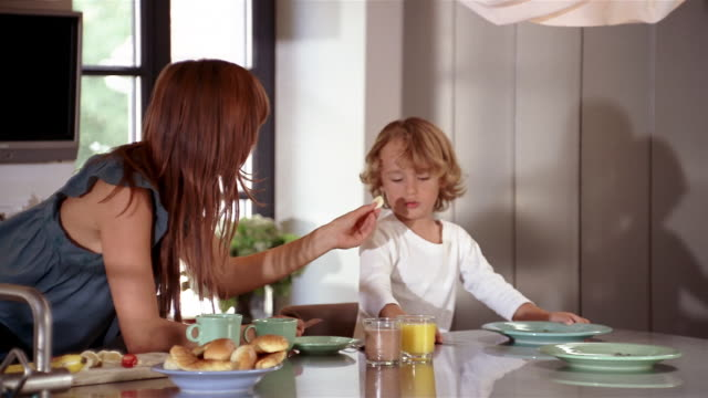 medium shot dolly shot mother trying to feed banana slice to young boy / child refusing and making faces - cucina domestica video stock e b–roll
