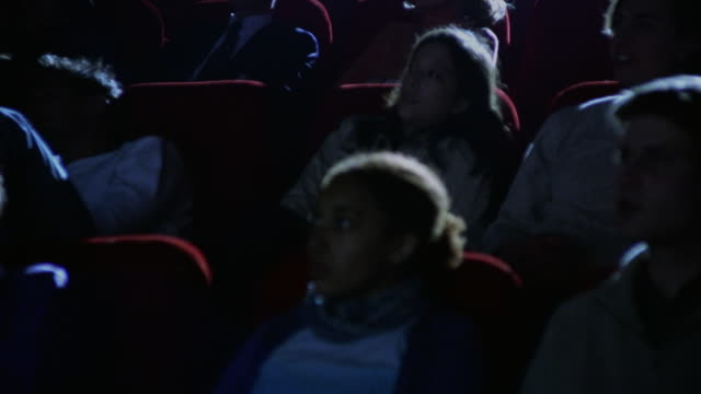 Medium shot dolly shot past audience intently watching movie in dark movie theater