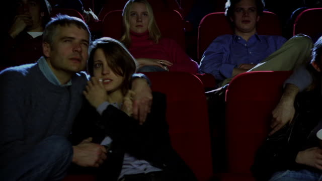 Medium shot dolly shot past audience watching horror film and looking scared in movie theater