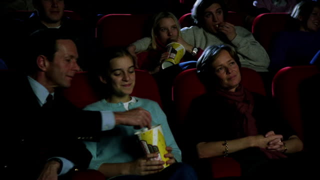 Medium shot dolly shot past audience watching intently in movie theater