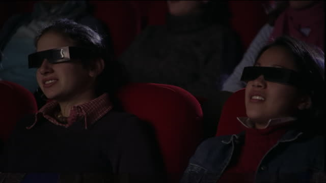 medium shot dolly shot past audience wearing 3-d glasses intently watching movie and smiling in theater - biosalong bildbanksvideor och videomaterial från bakom kulisserna