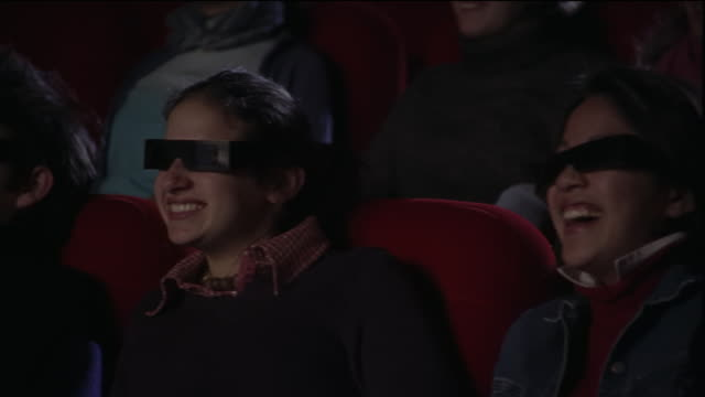 Medium shot dolly shot past audience wearing 3-D glasses watching movie intently and laughing in theater