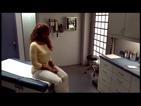 stockvideo's en b-roll-footage met medium shot dolly shot patient sitting on exam table in doctor's office / doctor greeting patient - onderzoekstafel