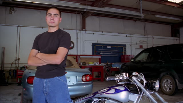 medium shot dolly shot portrait of young man standing behind motorcycle in garage - macho stock videos & royalty-free footage