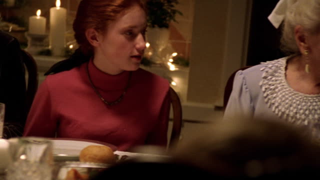 Medium shot dolly shot redheaded teenage girl handing grandmother gift at table during Christmas dinner / they hug