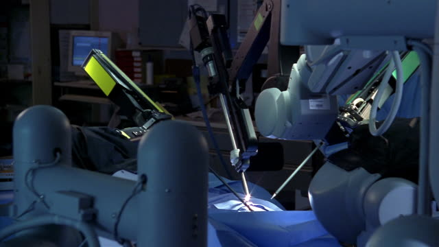 medium shot dolly shot robotic arms moving during robotic surgery - halbnahe einstellung stock-videos und b-roll-filmmaterial