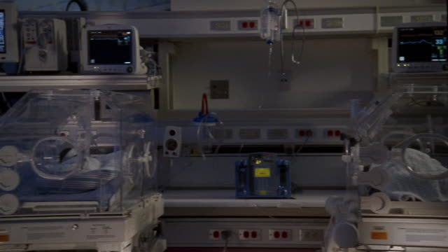 Medium shot dolly shot row of premature babies in incubators / ultraviolet light shining on incubator