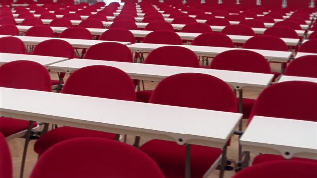 medium shot dolly shot rows of empty red chairs at white tables - auditorium stock videos and b-roll footage