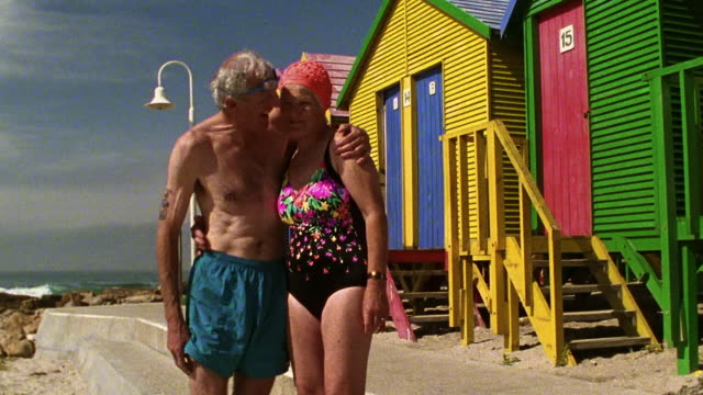 Medium shot dolly shot senior couple in swimsuits hugging by beach houses / St. James Beach, Cape Town, South Africa