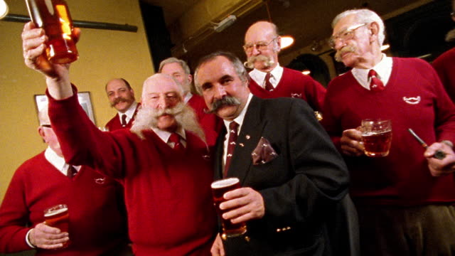 Medium shot dolly shot senior men wearing red sweaters and toasting with pints of beer / one talking