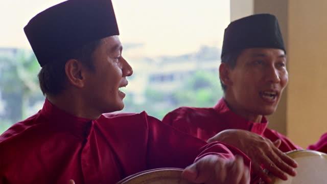vidéos et rushes de medium shot dolly shot three men wearing traditional red dress and playing instruments / maimoon palace medan, sumatra - robe rouge