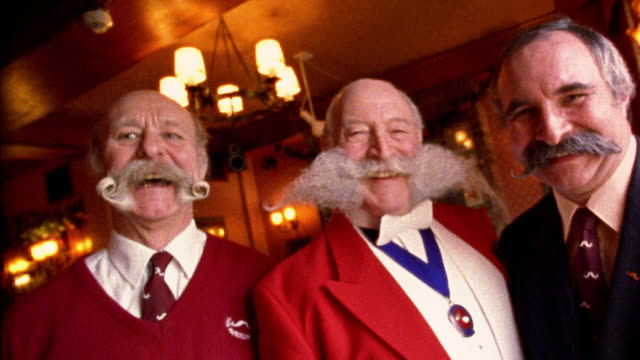 medium shot dolly shot three older british men with elaborate mustaches smiling / zoom in one kissing other on cheek - moustache stock videos and b-roll footage