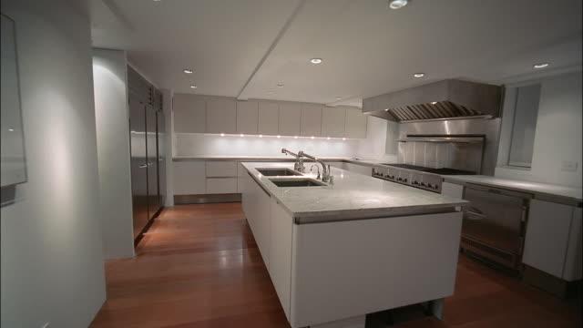 medium shot dolly shot through interior of empty showcase apartment kitchen - cupboard stock videos & royalty-free footage
